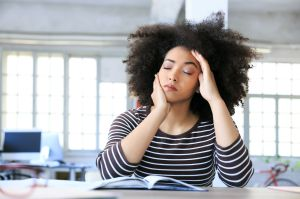 Young woman having headache at workplace