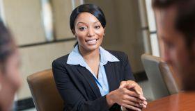 Three multi-racial office workers in boardroom