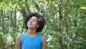 Young african american girl standing in a forest